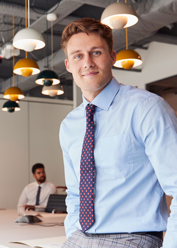 portrait of businessman standing in modern KERTNLY showing the concept of About Us
